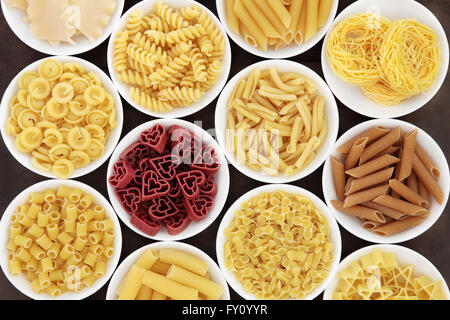 Italian dried pasta  shapes in white porcelain bowls. - Stock Photo
