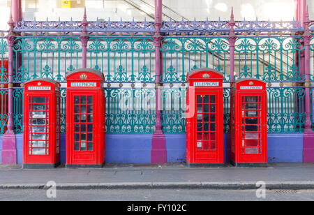 Traditional British red phone booths in a row at Smithfield Market in London - Stock Photo