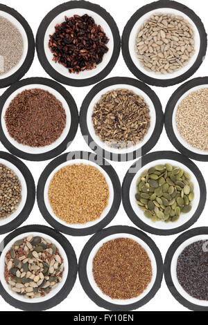 Seed food selection in porcelain bowls over slate rounds and white background. - Stock Photo