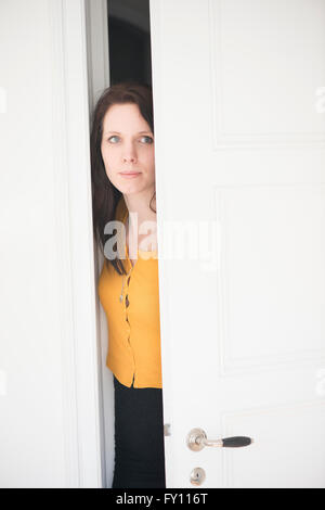 Serious woman opening door and looking. Concept of curiosity, suspicion and anxiety. - Stock Photo