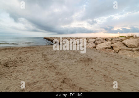 Long exposure picture of a Seawall in the beach at sunrise - Stock Photo