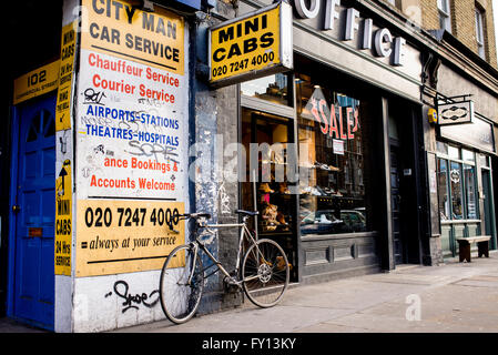 Mini cabs agency with old yellow billboards in a street in London. Bike parked in front. - Stock Photo