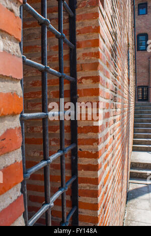 Barred window on a brick wall - Stock Photo
