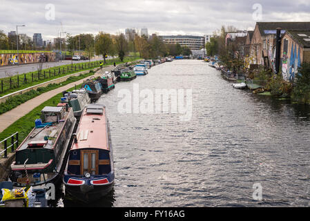 View of Regent's canal with canal boats converted to houses and footpath on the side - Stock Photo