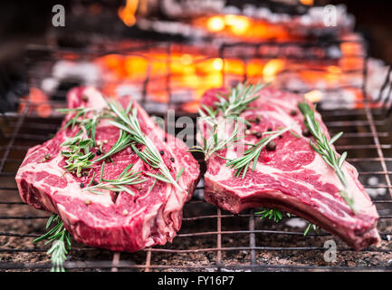 Rib eye steaks and grill with burning fire behind them. - Stock Photo