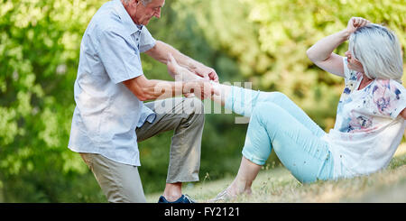 Senior man helps senior woman with sprained anke in the nature - Stock Photo