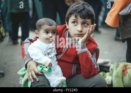Boy from Syria after arriving with his little brother, refugee camp in Idomeni, border with Macedonia, Greece - Stock Photo