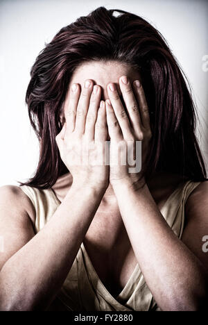 Young woman hiding face with her hands - Stock Photo