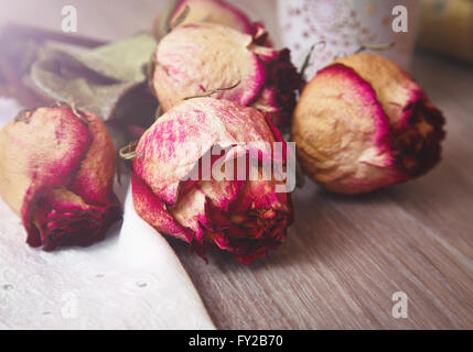 Dried rosebuds and lace on the table - Stock Photo