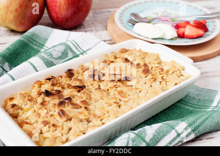 Apple crumble dessert with strawberries and vanilla cream on light rustic wooden background - Stock Photo