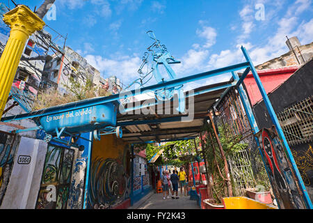 Horizontal view of tourists looking at the art installations inside Hamel's Alley in Havana, Cuba. - Stock Photo