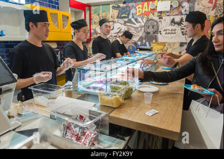 Workers in Yong Kang Street give out sushi samples in the Columbus Circle station in the subway in New York in the - Stock Photo
