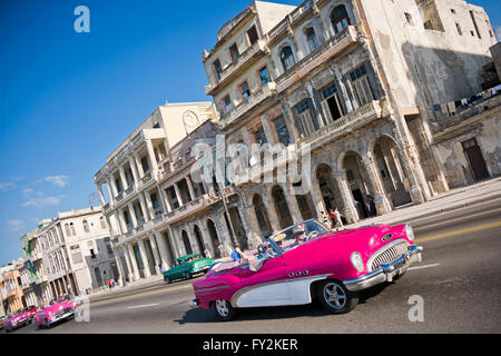 Horizontal view of classic American cars driving down the Malecon in Havana, Cuba. - Stock Photo