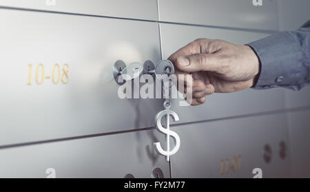 Safe deposit in a bank vault, hand about to turn a key to open a safe box. Financial concept - Stock Photo