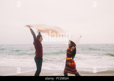 Funny young happy couple under the white blanket having fun and playfully look at each other. Winter beach on background. - Stock Photo