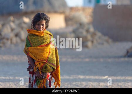 Traditionally dressed  unidentified young tribal woman stands and looks at the camera in rural areas near Thar desert - Stock Photo