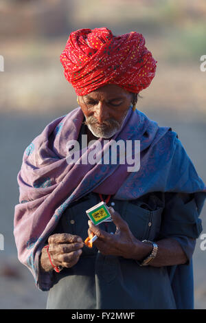 Traditionally dressed unidentified Indian tribal man looks at the camera with a strong character in his face, Jaisalmer, - Stock Photo