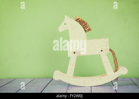 vintage rocking horse on wooden floor. retro filtered image. - Stock Photo
