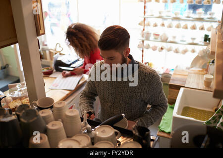 Young Couple Working In Coffee Shop - Stock Photo