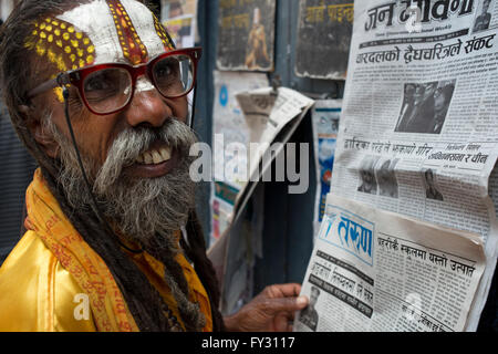 Nepalese hindu holy man reading newspapers near Basantapur, Kathmandu, Nepal - Stock Photo