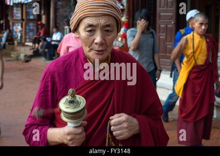 Man with a prayer mill at Boudhanath Stupa, Kathmandu, Nepal. Prayer mill, Bodhnath Stupa, Kathmandu, Nepal, Asia - Stock Photo