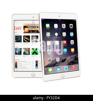 Two Apple iPad Mini 3 tablets with desktop and iTunes store on their displays - Stock Photo