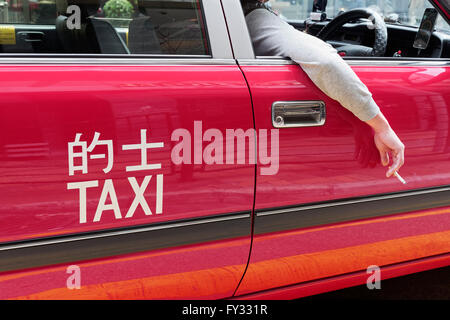 Red Hong Kong taxi, wheel on the right side, driver's hand with cigarette out the window, Hong Kong, China - Stock Photo