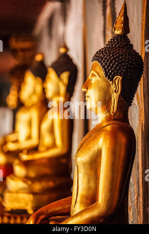 Gold sitting Buddha statues in Thailand - Stock Photo