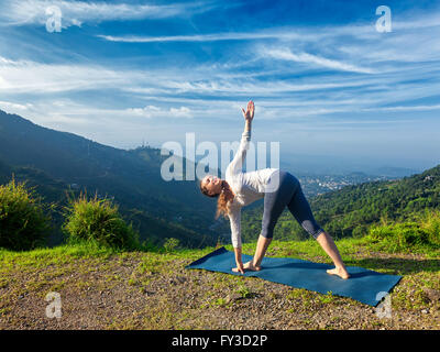 woman doing yoga asana parivrtta janu sirshasana stock