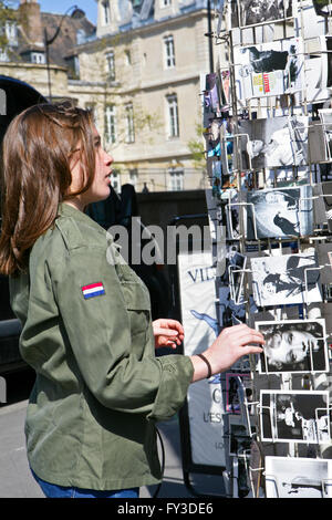 Young l girl looking at postcards in the streets of Paris, France - Stock Photo