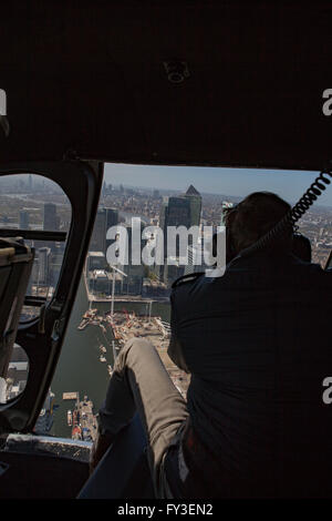 View from inside of Helicopter with door open over London during aerial photography trip - Stock Photo