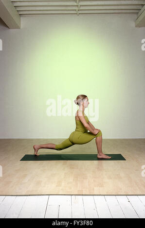 Stay Young Lunge Warrior woman returning to all-fours position on green mat profile straight right leg stepped forward - Stock Photo