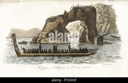 Maoris in a war canoe in front of a pa on an arched rock in New Zealand. The fortified village or pa is atop the - Stock Photo
