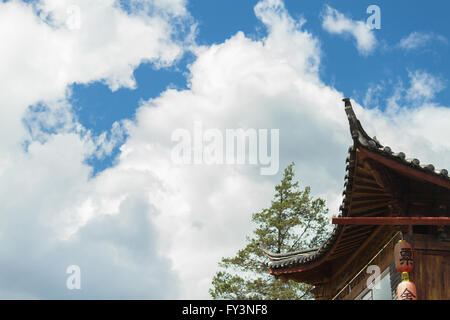 Chinese traditional curved roof (sweeping curvature) with red lanterns against cloudy sky in Yunnan province - Stock Photo