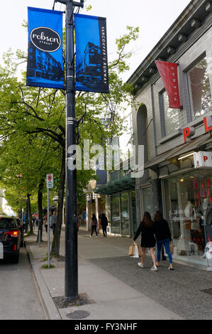 Two young Asian women walking along Robson Street, a popular  shopping district in downtown Vancouver, BC, Canada - Stock Photo