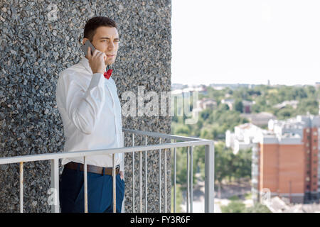 Serious Groom talking by phone - Stock Photo