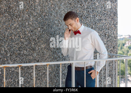 Happy Groom talking by phone - Stock Photo