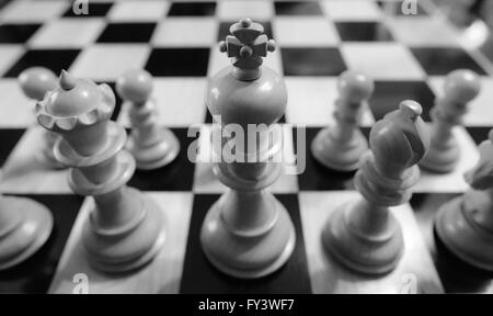 Hand-carved chess pieces ready to do battle on the chess board - Stock Photo