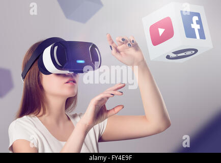 Varna, Bulgaria - March 10, 2016: Woman in VR headset looking up and interacting with Facebook Youtube Steam VR - Stock Photo