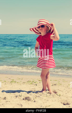 Funny little girl  on the beach. The image is tinted. - Stock Photo