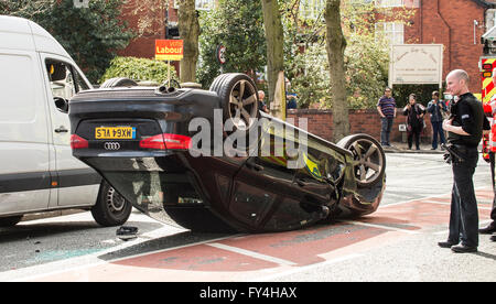 Car accident black Audi upside down with Police and Firemen looking on in disbelief - Stock Photo
