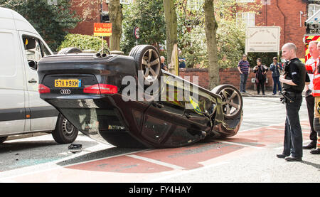 Car crash, black audi upside down with white van alongside, vote Labour election banner behind, police and fire - Stock Photo
