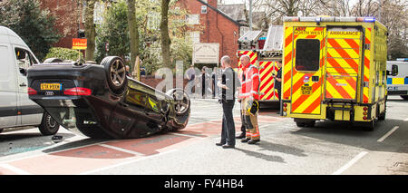 Black Audi car upside down, white transit, labour party banner, ambulance, policeman, firemen, fire engine, police - Stock Photo