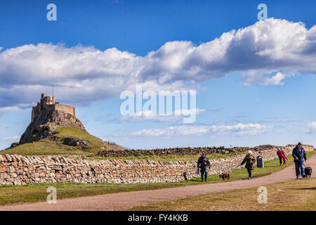 People walking down the track from Lindisfarne Castle, Holy Island, Northumberland, UK, on a bright spring day. - Stock Photo