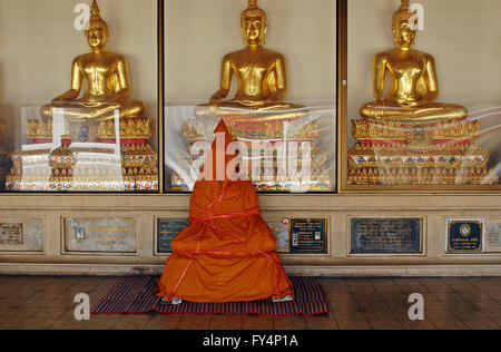 A new buddhist statue is wrapped in orange robes waiting to be delivered sits in front of three gleaming gold buddahs - Stock Photo