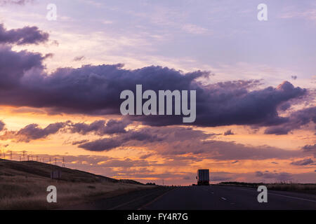 Scenes along Interstate 5 near Patterson California late in the day with car and truck traffic and the sun - Stock Photo