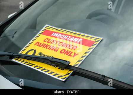 Notice on the windscreen of a car belonging to a member of staff, warning that the area is for customer parking - Stock Photo