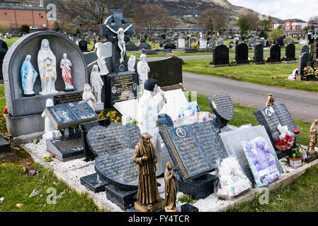 A large number of marble memorial stones on a grave in an Irish graveyard, including a large statue of Elvis Presley. - Stock Photo