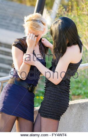 Pretty girlfriends compassion friendship short mini skirt clothing upset empathy girls teen crushed young-woman - Stock Photo