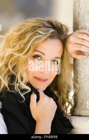 Attractive young woman in Black portrait curly hair blonde inclined smiling smile positive feeling mood curls curly - Stock Photo